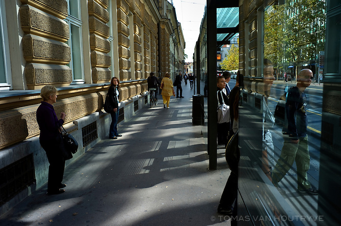 People wait at a bus stop in Ljubljana, Slovenia on Oct. 21, 2011.