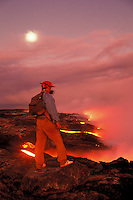 Man wearing a  gas mask while standing near fumes and lava flow to the sea form Kilauea Volcano, Big Island of Hawaii