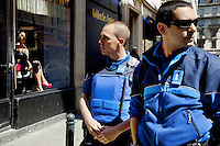 "Switzerland. Geneva. Pedestrian patrol. Two police officers walk at daytime on the streets of the Paquis neighborhood, known for its Red-light district. Street prostitution. Most of the prostitutes work in the streets. Others wait inside seated  and look through the windows for customers. Prostitution is often referred to as ""the world's oldest profession"". Both policemen are wearing a ballistic vest, bulletproof vest or bullet-resistant vest which is an item of personal armor that helps absorb the impact from knives, firearm-fired projectiles and shrapnel from explosions, and is worn on the torso. Soft vests are made from many layers of woven or laminated fibers and can be capable of protecting the wearer from small-caliber handgun and shotgun projectiles. Both policemen have also a two-way radio which is a radio that can both transmit and receive (a transceiver). A two-way radio (transceiver) allows the operator to have a conversation with other similar radios operating on the same radio frequency (channel). Two-way radios are available with hand-held portable configurations. Hand-held radios are often called walkie-talkies or handie-talkies. 14.05.12 © 2012 Didier Ruef"