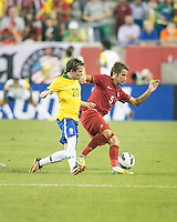 Portugal defender Fabio Coentrao (5) fends off Brazil midfielder Bernard (20) as he comes in for a tackle.  In an International friendly match Brazil defeated Portugal, 3-1, at Gillette Stadium on Sep 10, 2013.