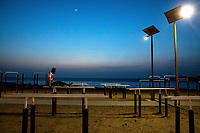 Chinese supplied solar lights illuminate exercise machines on the beach.