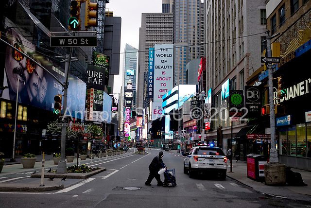 """New York, New York<br /> April 4, 2020<br /> <br /> The 7th Avenue Times Square with all theaters shut down.<br /> <br /> The coronavirus has transformed urban architectural spaces with fear of proximity. Not entirely void of humanity, social distancing, within expansive city environments has created a landscape of aggrandizing physical structures and expanding spaces while diminishing the scale of humans. Face masks enhance the anonymity of """"the person"""", reducing them to a figure or an uninterrupted shadow falling on a surface."""