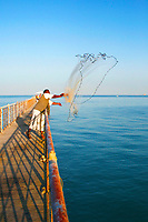 Fisherman waring traditional outfit, throwing his fish net during a sunny day, just before sunset/ sundown.