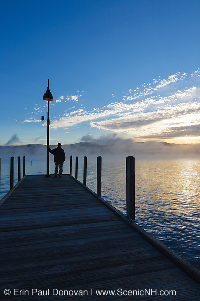Wellington State Park - The silhouette of a man on dock watching sunrise over Newfound Lake in Bristol, New Hampshire USA