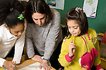 Education Elementary School Grade 2 female teacher working with two female students science social studies project horizontal