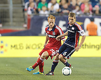 New England Revolution midfielder Scott Caldwell (6) dribbles as Chicago Fire midfielder Jeff Larentowicz (20) defends. In a Major League Soccer (MLS) match, the New England Revolution (blue) defeated Chicago Fire (red), 2-0, at Gillette Stadium on August 17, 2013.