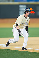 Conor Keniry (14) of the Wake Forest Demon Deacons takes his lead off of third base against the Cincinnati Bearcats at Wake Forest Baseball Park on February 21, 2014 in Winston-Salem, North Carolina.  The Bearcats defeated the Demon Deacons 5-0.  (Brian Westerholt/Four Seam Images)