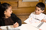 Education preschoool children ages 3-5 art activity boy showing girl his drawing and listening to her encouraging comment horizontal