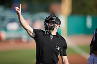 Home plate umpire Lane Cullipher signals to the press box that the Augusta GreenJackets used their first mound visit during the game against the Charleston Boiled Peanuts at Joseph P. Riley, Jr. Park on June 26, 2021 in Charleston, South Carolina. (Brian Westerholt/Four Seam Images)