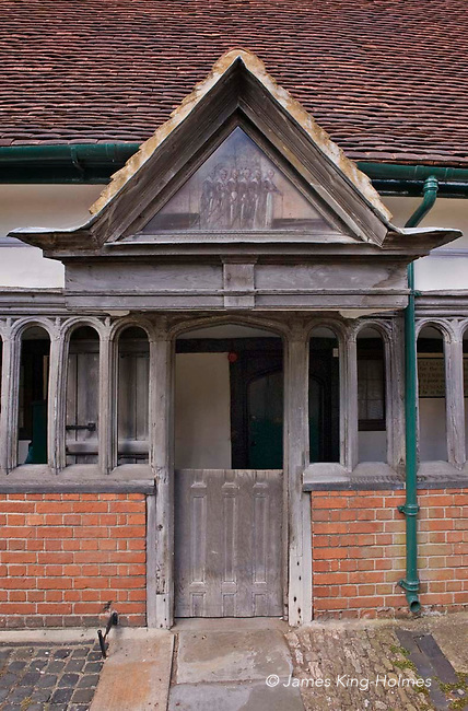 Doorway at the Long Alley Almshouses in Abingdon, Oxfordshire, UK, parts of which were built in the 15th & 16th centuries. Above the door the triangular panel represents six almswomen and is believed to be painted by Sampson Strong (1550-1611).They dwellings were founded  by the medieval Fraternity of the Holy Cross which started the building work in 1446/47 and are now administered by the Christ's Hospital charity, founded in 1553.