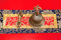 Bodhnath, Nepal.  Bell and Vajra on a Table Runner at the Tsamchen Gompa (Tibetan Buddhist Monastery).  The vajra is a ritual tool representing a thunderbolt or a diamond, symbolizing firmness of spirit.  This tool is used in Buddhism, Hinduism, and Jainism.