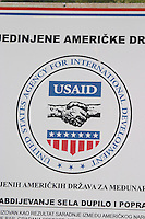 sign saying that USAid is giving financial aid to this region. Near Dupilo, Golubovic Montenegro, Balkan, Europe.