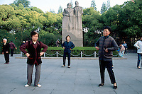 """China. Shanghai. Downtown. City center. Fuxing Park. Fuxing means revival. Early morning a group of chinese women are doing their daily exercices. They practise """" Tai Chi"""" (chinese martial art) near the statue of Karl Marx and Friedrich Engels .  © 2002 Didier Ruef"""