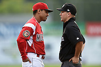 Batavia Muckdogs manager Angel Espada (4) argues a call with umpire Chris Scott during a game against the Staten Island Yankees on August 7, 2014 at Dwyer Stadium in Batavia, New York.  Staten Island defeated Batavia 2-1.  (Mike Janes/Four Seam Images)
