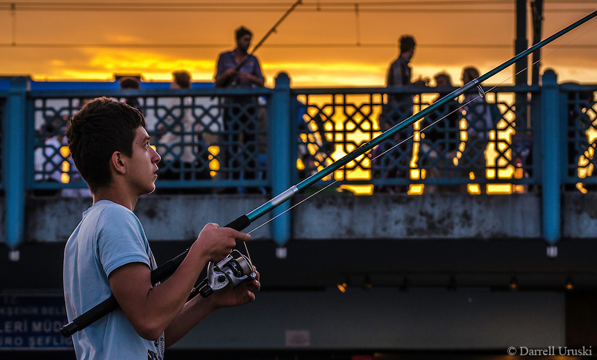 Urban Street Photograph of a young boy getting ready to go fishing during a golden sunset from the Galata Bridge in Istanbul, Turkey.