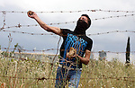 A Palestinian protester hurls stones toward Israeli soldiers during the weekly demonstration against Israel's controversial separation barrier in the village of Bilin, near the West Bank city of Ramallah on April 22, 2011. Some 250 left-wing Israeli and foreign activists protested in the West Bank village of Bilin against the separation fence being built in the area. Some of the protestors hurled stones at the security forces, who used crowd dispersal means in response. Photo by Issam Rimawi