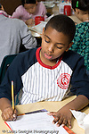 Education Elementary Public school grade 4 class with science specialist male student working in class vertical