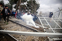 Pictured: FYRO Macedonian police throw smoke grenades to the refugees that threw stones and battered down the barbed wire gate of the fence Monday 29 February 2016<br /> Re: A crowd of migrants has burst through a barbed-wire fence on the FYRO Macedonia-Greece border using a steel pole as a battering ram.<br /> TV footage showed migrants pushing against the fence at Idomeni, ripping away barbed wire, as FYRO Macedonian police let off tear gas to force them away.<br /> A section of fence was smashed open with the battering ram. It is not clear how many migrants got through.<br /> Many of those trying to reach northern Europe are Syrian and Iraqi refugees.<br /> About 6,500 people are stuck on the Greek side of the border, as FYRO Macedonia is letting very few in. Many have been camping in squalid conditions for a week or more, with little food or medical help.