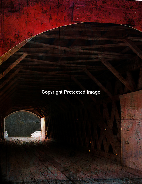 You can see daylight on the other side of an old covered bridge in Madison County, Iowa.