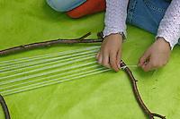 Kinder weben ein Blumenbild, Mädchen hat einen Rahmen aus Ästen gebaut und spannt Wolle dazwischen