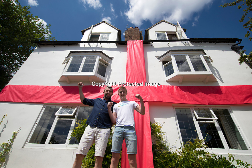 """***CAPTION CORRECTION***<br /> <br /> 08/07/18<br /> <br /> Robin Cantellow with his son Jonny.<br /> <br /> As more of the country gets behind the English team, Robin Cantellow (54) adorns his four bedroomed 17th century house with a ten by five metre giant ribbon in Ashbourne, Derbyshire.<br /> <br /> """"I put it up yesterday before the match and that worked, so I'm keeping it up for another week - hopefully""""<br /> All Rights Reserved, F Stop Press Ltd. (0)1335 344240 +44 (0)7765 242650  www.fstoppress.com rod@fstoppress.com"""