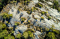 Aerial view of a group of mountain bikers riding a trail across granite slab in the Änggårdsbergen Nature Reserve, Gothenburg, Sweden