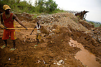 Artisanal  Miners sift through the  tailings in the shadow of  an abandoned processing  plant in Kanga, outside Mongbwalu, north-eastern DRC..The tailings are bits of stone and silt left over from the refinery process. This processing plant was  the central refinery for gold found in Ituri province. Even during  the war it was pushing out 10-20 kilos of gold per month. .The shell of the buildings and the waste left behind are all that remain the company fled during the war. Since being abandoned in 2001 anything that could be carried away and used elsewhere or sold as scrap has disappeared..