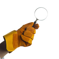 A yellow/brown gauntlet holding a magnifying glass