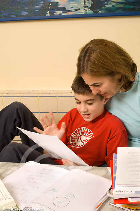 11 year old boy frustrated over homework assignment, mother talking him through it, boy defining the problem, talking