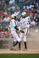 Taylor Trammell (5) of Mt. Paran Christian High School in Powder Springs, Georgia and Delvin Perez (1) of International Baseball Academy in Loiza, Puerto Rico celebrate a run during the Under Armour All-American Game on August 15, 2015 at Wrigley Field in Chicago, Illinois. (Mike Janes/Four Seam Images)
