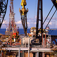 Slinging 800 ton module onto gigantic crane hook for lift onto oil production platform with 4,000 ton crane.  North Sea..