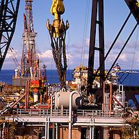 Slinging 800 ton module onto gigantic crane hook for lift onto oil production platform with 4,000 ton crane.  North Sea..