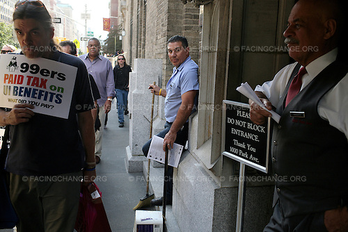 "New York City.October 11th, 2011..Doorman who have been handed leaflets watch as ""Occupy Wall Street"" protestors march through New York City's wealthy Upper East Side neighborhood to visit the homes of five billionaires, Rupert Murdoch, David Koch, Howard Milstein, John Paulson, and Jamie Dimon, all people who they claimed have not paid their fair share of taxes."