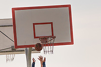 A basketball frozen in midair over the grasping hands of players under the hoop and backboard at a neightborhood park on a spring afternoon.