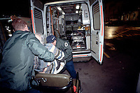 Paramedic ambulance crew lifting an elderly casualty out of the ambulance and into a wheelchair so as he can be brought into the accident and emergency unit of the hospital.