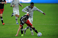 WASHINGTON, DC - NOVEMBER 8: Russell Canouse #4 of D.C. United battles for the ball with Romell Quioto #30 of Montreal Impact during a game between Montreal Impact and D.C. United at Audi Field on November 8, 2020 in Washington, DC.