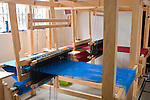 Large, free standing loom with bright blue yarn in a woman's cooperative in Zunil, Guatemala in the Western Highlands
