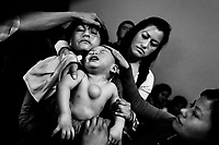 A Colombian mother holds her baby boy, having a tumor in his chest, during the religious healing ritual performed at a house church in Bogota, Colombia, 28 January 2013. Hundreds of Christian belivers, joined in nameless groups, gather every week in unmarked home churches dispersed in the city outskirts, to carry out prayers of liberation and exorcism. Community members and their religious activities are usually conducted by a charismatic pastor or preacher. Using either non-contactive methods (reading religous formulas from bible, displaying Christian symbols and icons) or rough body-pressure-points techniques and forced burping, a leading pastor commands the supposed evil spirit, which is generally believed to come from witchcraft, to depart a person's mind and body. The demon's expulsion often consists of multiple rites and may last for several months.