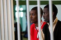 Da sinistra, Mohamed Isse Karshe ed Abdi Hassan Mahamur, presunti pirati somali accusati dell'attacco alla nave portacontainer italiana Montecristo, durante la prima udienza del processo presso la III Corte d'Assise a Roma, 23 marzo 2012. La nave, assaltata il 10 ottobre 2011 al largo della Somalia, venne liberata il 15 ottobre dai Royal Marines britannici con l'ausilio di una nave militare statunitense..Somali allegedly pirates, from left, Mohamed Isse Karshe and Abdi Hassan Mahamur sit inside a cage during the opening audience for the assault to the Montecristo container ship, in Rome, 23 march 2012. The ship was attacked on 10 october 2011 and freed by US navy and British Royal Marines on 15 october..UPDATE IMAGES PRESS/Riccardo De Luca