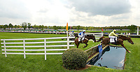 Wide angle view showing the grounds as jockey's and their horses complete a jump over water during the Queen's Cup Steeplechase in Mineral Springs, NC.