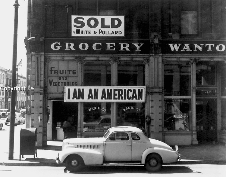"""Following evacuation orders, this store was closed.   The owner, a University of California graduate of Japanese descent, placed the """"I AM AN AMERICAN"""" sign on the store front the day after Pearl Harbor.  Oakland, CA, April 1942.  Dorothea Lange. (WRA)<br /> Exact Date Shot unknown<br /> NARA FILE #:  210-G-2A-35<br /> WAR & CONFLICT #:  772"""