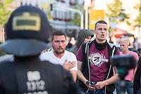 """Ca. 500 Menschen demonstrierten am Freitag den 31. Juli 2015 im Saechsischen Feital gegen Rassismus und fuer die Aufnahme von Fluechtlingen.<br /> Nach mehreren Wochen rassistischer Uebergriffe und Bedrohungen durch einen Teil der Freitaler Bevoelkerung war dies ein Zeichen der Solidaritaet mit den gefleuchteten Menschen.<br /> Am Rande der Demonstration kam es immer wieder zu rassistischen Poebeleien, Flaschenwuerfen und versuchten Angriffen auf die Demonstranten durch Neonazis und Hooligans die sich vor ihrer Stammkneipe """"Timba"""" versammelt hatten. Vereinzelt ging die Polizei gegen die Rechten vor und nahm mindestens eine Person wegen zeigen eines Hitlergrusses fest. Die Flaschenwuerfe blieben fuer die Rechten folgenlos.<br /> Im Bild: Polizei haelt Neonazis von der antirassistischen Demonstration fern. Mit weinrotem T-Shirt, ein Mitglied der NPD-Jugendorganisation Junge Nationaldemokraten (JN).<br /> 31.7.2015, Freital/Sachsen<br /> Copyright: Christian-Ditsch.de<br /> [Inhaltsveraendernde Manipulation des Fotos nur nach ausdruecklicher Genehmigung des Fotografen. Vereinbarungen ueber Abtretung von Persoenlichkeitsrechten/Model Release der abgebildeten Person/Personen liegen nicht vor. NO MODEL RELEASE! Nur fuer Redaktionelle Zwecke. Don't publish without copyright Christian-Ditsch.de, Veroeffentlichung nur mit Fotografennennung, sowie gegen Honorar, MwSt. und Beleg. Konto: I N G - D i B a, IBAN DE58500105175400192269, BIC INGDDEFFXXX, Kontakt: post@christian-ditsch.de<br /> Bei der Bearbeitung der Dateiinformationen darf die Urheberkennzeichnung in den EXIF- und  IPTC-Daten nicht entfernt werden, diese sind in digitalen Medien nach §95c UrhG rechtlich geschuetzt. Der Urhebervermerk wird gemaess §13 UrhG verlangt.]"""