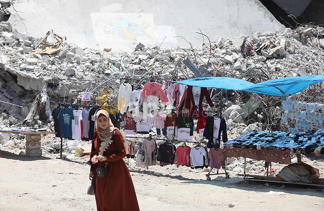Palestinian street vendors display their goods near the rubble of al-Shuruq tower in Gaza City, on July 17, 2021. Al-Rimal neighbourhood which was targeted by Israeli strikes during the recent confrontations between Hamas and Israel. Photo by Ashraf Amra