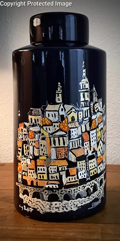 """""""Menton""""<br /> <br /> The hand painted coastal town of Menton, France, bordering Italy, is permanently affixed to this navy blue jar with lid. Reflective enamel automotive paints make for a stunning display and are very easy to clean.<br /> <br /> 12""""x 6""""<br /> $2,800"""