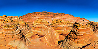 The Wave's iconic, stunning sandstone formations panorama under a blue sky, in North Coyote buttes of Paria Canyon, at the Arizona and Utah border USA