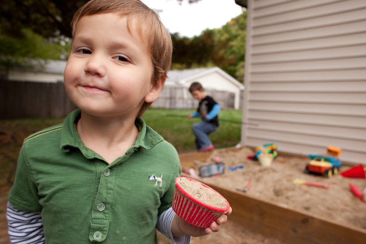 My younger son, age three, shows off a cupcake from our sandbox.