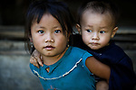 A young girl carries her baby brother on her back in rural Laos, near Luang Prabang. Often older siblings are responsible to watch their younger brothers and sisters throughout the day.
