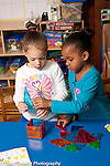 Education Preschool Headstart 4 year olds two girls working together building structure from colorful flat magnetic blocks