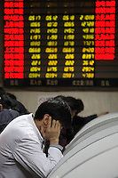 An investor looks into his computer terminal at a securities exchange house in Shanghai, China..22 Jan 2008
