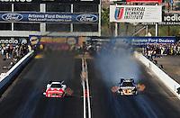 Oct. 16, 2011; Chandler, AZ, USA; NHRA funny car driver Johnny Gray (left) races alongside a tire smoking Matt Hagan during the Arizona Nationals at Firebird International Raceway. Mandatory Credit: Mark J. Rebilas-